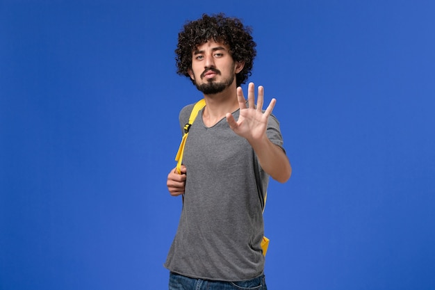 Front view of young male in grey t-shirt wearing yellow backpack smiling on blue wall