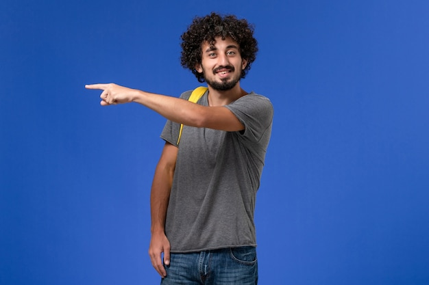 Front view of young male in grey t-shirt wearing yellow backpack smiling on the blue wall