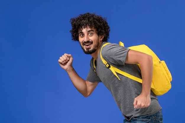 Front view of young male in grey t-shirt wearing yellow backpack smiling and running on the blue wall