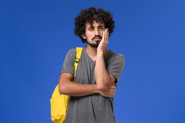 Front view of young male in grey t-shirt wearing yellow backpack thinking on the blue wall
