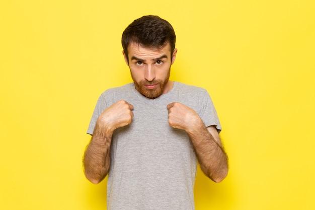 Un giovane maschio di vista frontale in maglietta grigia con l'espressione confusa sul colore giallo di emozione di espressione dell'uomo della parete