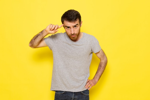 A front view young male in grey t-shirt with thinking expression on the yellow wall man expression emotion color