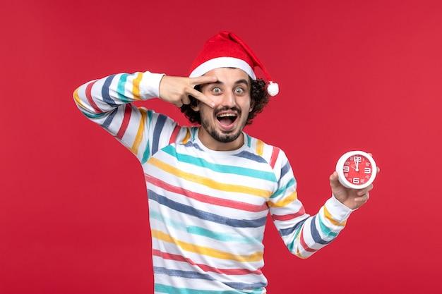 正面図若い男性は幸せに赤い壁時間新年の休日の赤い男性の時計を保持しています