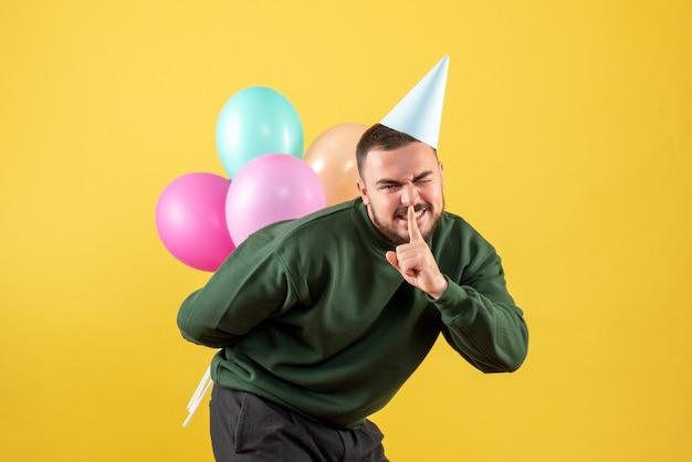 Vista frontale giovane maschio nascondendo palloncini colorati dietro la schiena su sfondo giallo