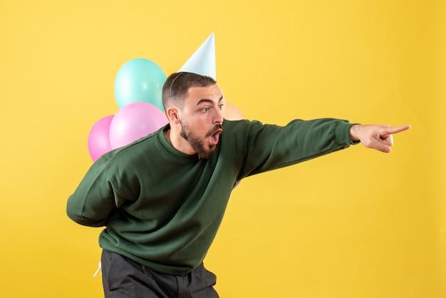 Vista frontale giovane maschio nascondendo palloncini colorati dietro la schiena su giallo