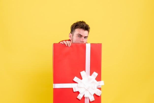 プレゼントボックスの中に隠れている正面図若い男性 無料写真