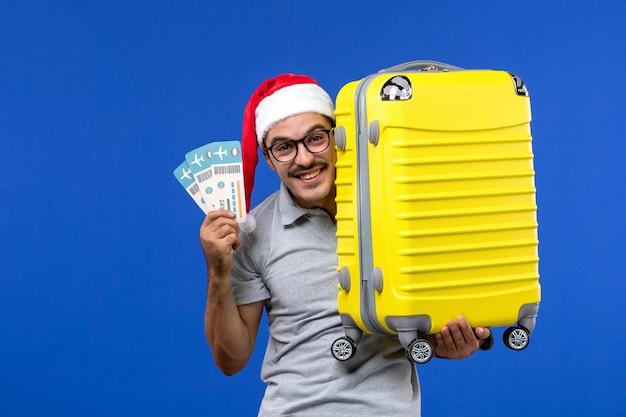 青い壁の男性の飛行休暇の飛行機のバッグとチケットを保持している若い男性の正面図