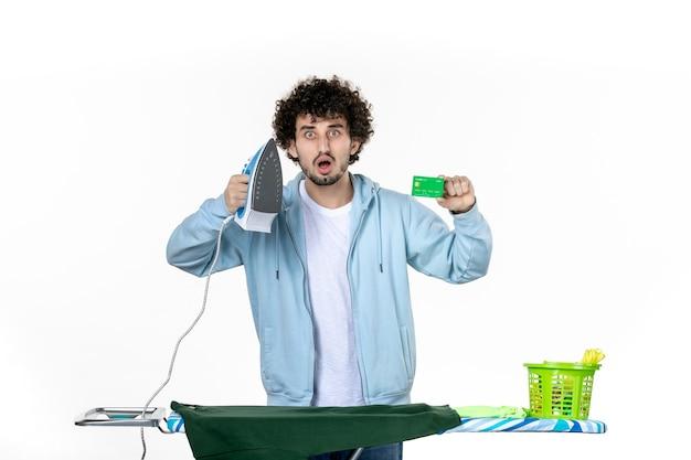 전면보기 젊은 남성 흰색 배경에 은행 카드와 철을 들고 세탁 가사 색상 인간의 철 청소 돈 감정