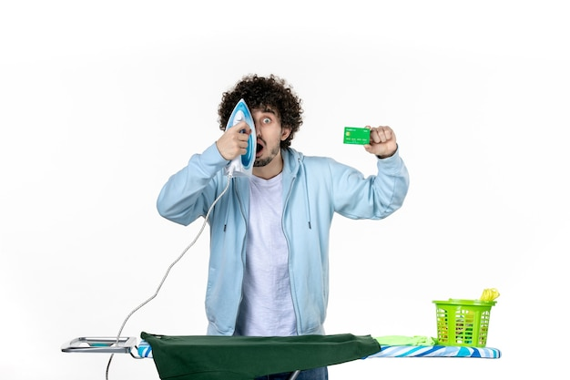 전면보기 젊은 남성 흰색 배경에 은행 카드와 철을 들고 세탁 가사 색상 인간의 철 청소 감정