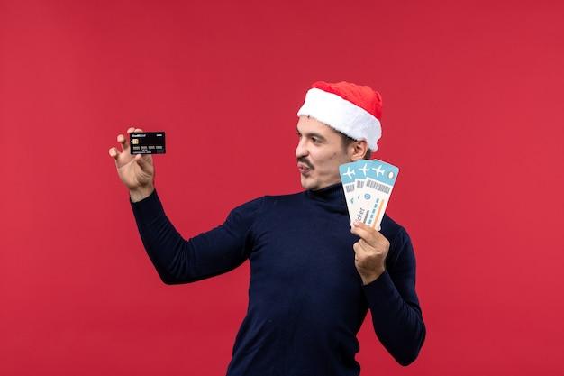 Вид спереди молодой мужчина держит банковскую карту и билеты на красном фоне