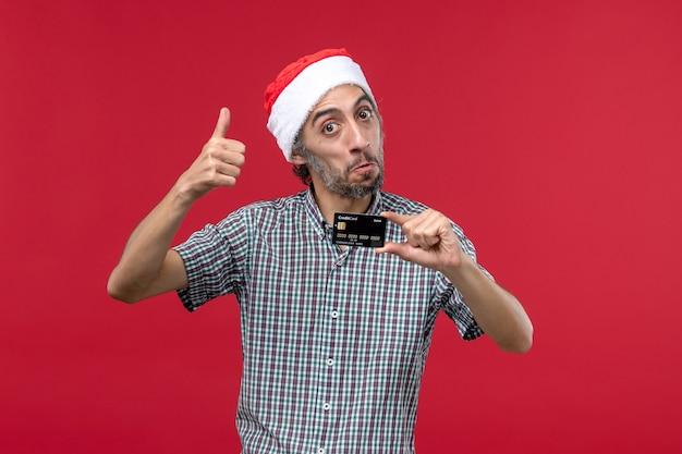 赤の背景に銀行カードを保持している若い男性