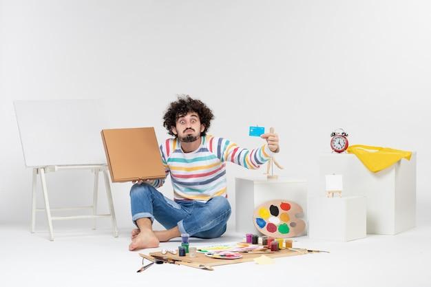 Vista frontale del giovane maschio che tiene la carta di credito e la scatola della pizza sul muro bianco