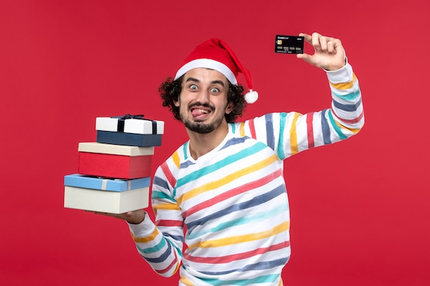 Front view young male holding bank card and presents on red desk new year money red