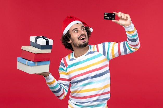 Front view young male holding bank card and presents on red wall new year money red male