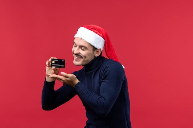 Vista frontale giovane maschio in possesso di carta bancaria su sfondo rosso