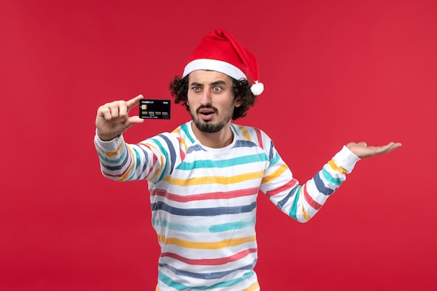 Front view young male holding bank card on red desk emotion red male holiday