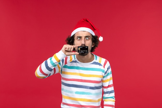 Front view young male holding bank card on red wall male red holidays emotions