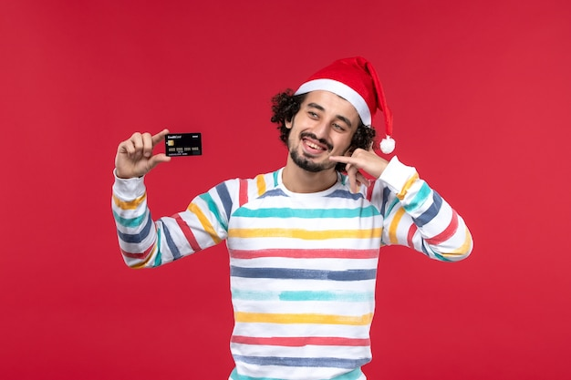 Front view young male holding bank card on red wall money red male emotion holiday