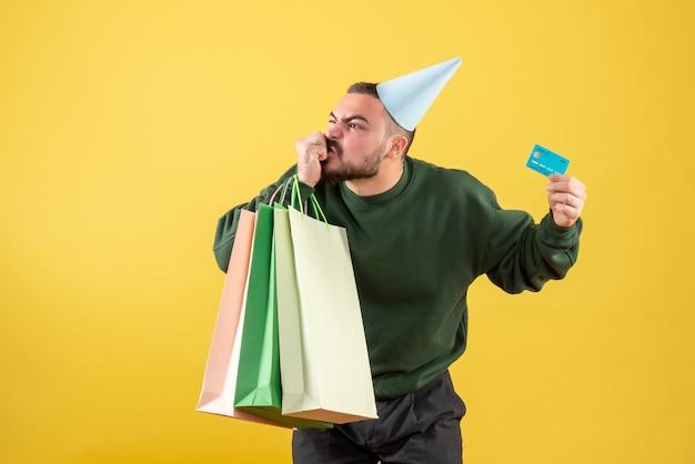 Vista frontale giovane maschio in possesso di carta bancaria e pacchetti della spesa su sfondo giallo