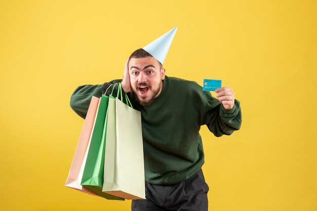 Front view young male holding bank card and shopping packages on yellow