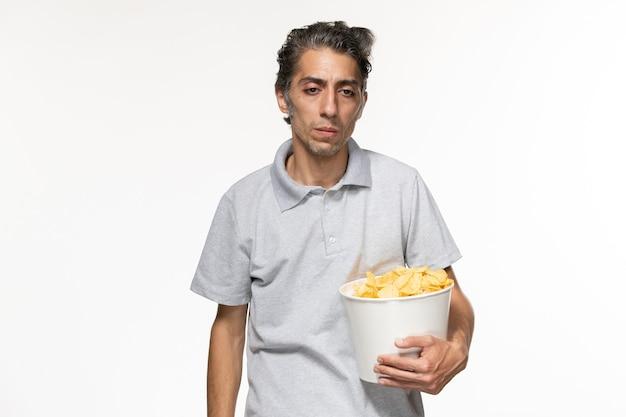 Вид спереди молодого мужчины, держащего корзину с картофельными чипсами и подчеркнутого на белой поверхности