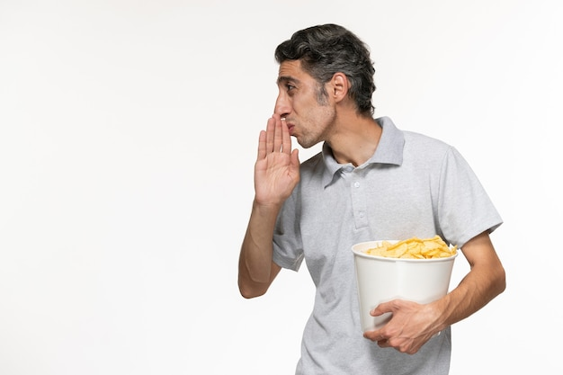 Вид спереди молодой мужчина, держащий корзину с картофельными чипсами, разговаривает с кем-то на белой поверхности