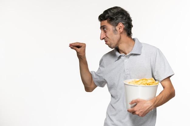 흰색 표면에 누군가에게 얘기하는 감자 칩 전면보기 젊은 남성 지주 바구니