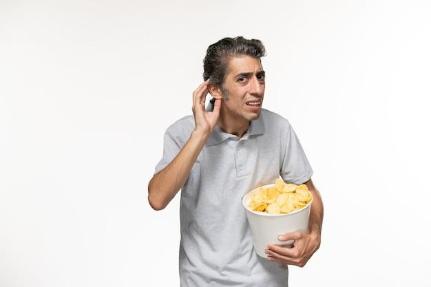 正面図ポテトチップスとバスケットを保持し、白い表面で聞くことを試みている若い男性