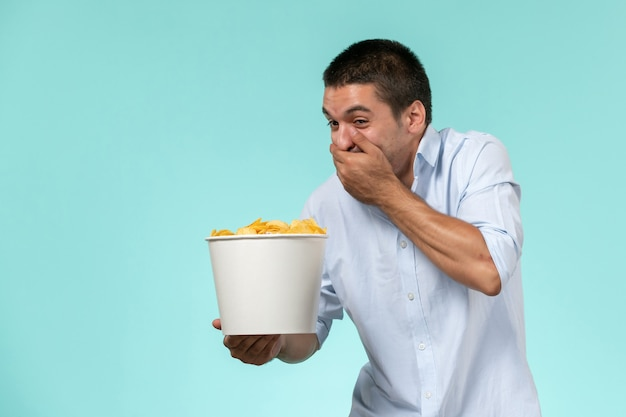 Front view young male holding basket with potato chips and laughing on a blue surface