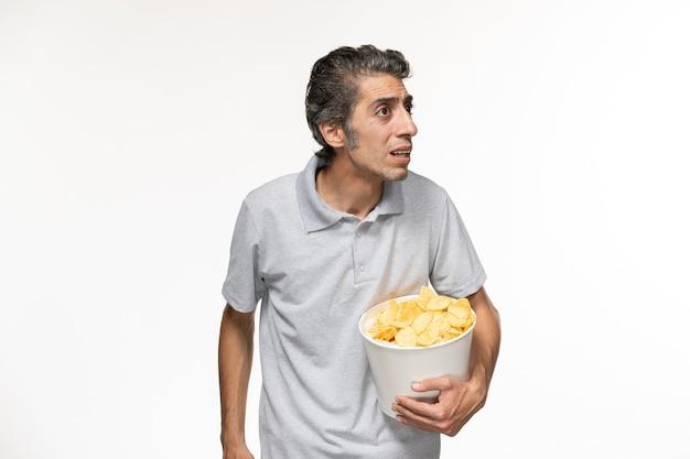 Cestino maschio giovane della tenuta di vista frontale con le patatine fritte sulla superficie bianca chiara