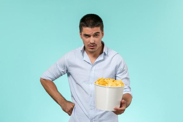 Вид спереди молодого мужчины, держащего корзину с картофельными чипсами на синей поверхности