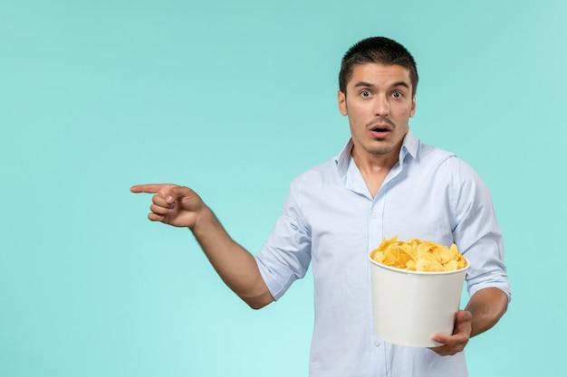파란색 표면에 감자 칩 전면보기 젊은 남성 지주 바구니