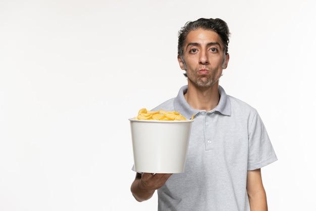 Вид спереди молодого мужчины, держащего корзину с картофельными чипсами на светлой белой поверхности