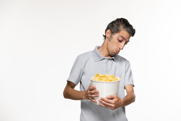 흰색 표면에 감자 칩 전면보기 젊은 남성 지주 바구니