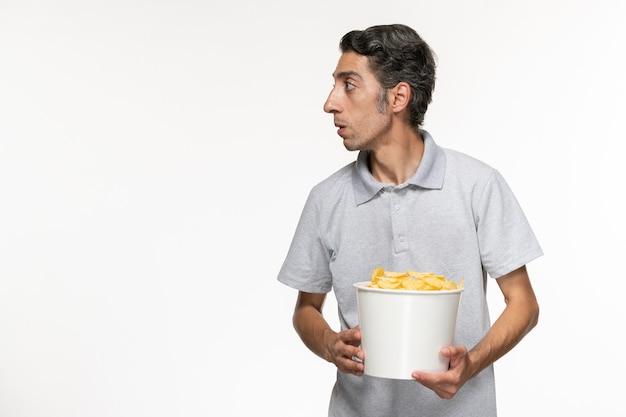 Вид спереди молодого мужчины, держащего корзину с картофельными чипсами на белом столе