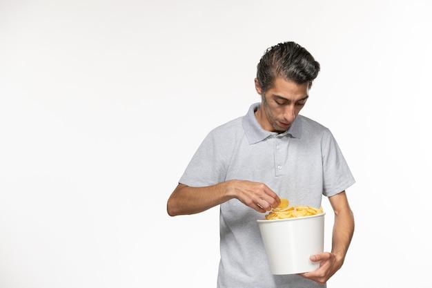 Вид спереди молодого мужчины, держащего корзину с картофельными чипсами на белой поверхности