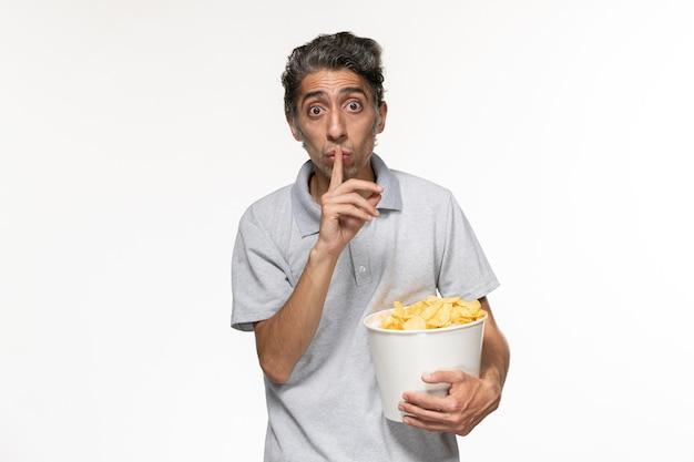 Cestino maschio giovane della tenuta di vista frontale con le patatine fritte sullo scrittorio bianco