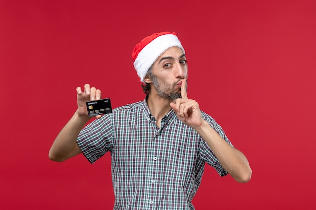 Вид спереди молодой мужчина держит черную банковскую карту на красном фоне