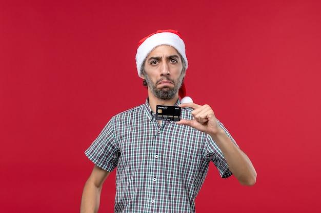 赤い背景に黒い銀行カードを保持している正面図若い男性