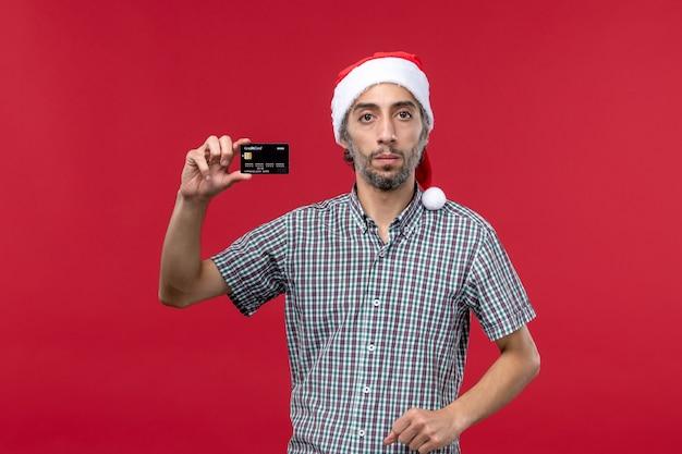 빨간색 배경에 검은 은행 카드를 들고 전면보기 젊은 남성