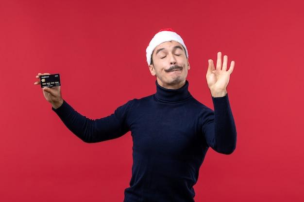 赤い机の上に黒い銀行カードを保持している正面図若い男性