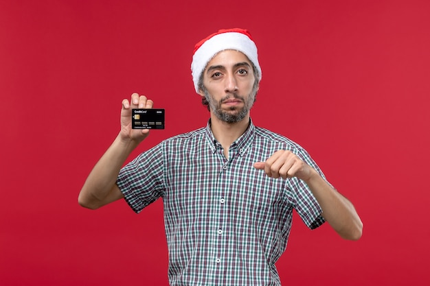 Giovane maschio di vista frontale che tiene la carta di credito nera sui precedenti rossi