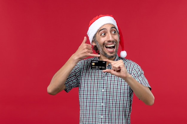 Front view young male holding black bank card on red background