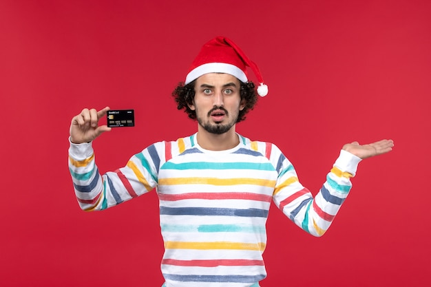 Front view young male holding black bank card on red wall money red male emotions holidays