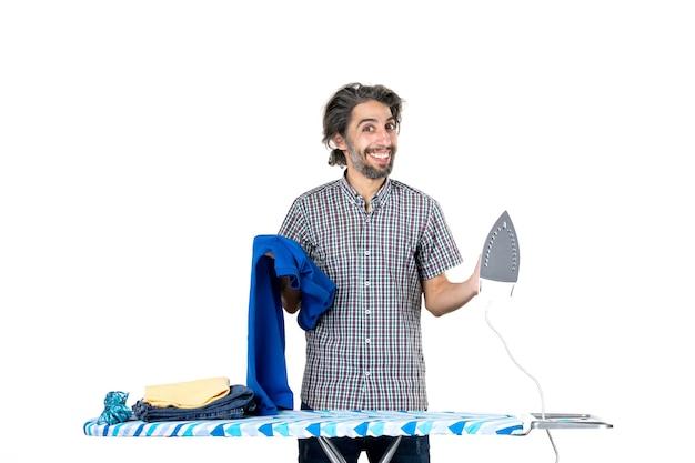 흰색 배경에 파란색 셔츠와 철을 들고 전면 보기 젊은 남성 집 남자 색상 깨끗한 기계 옷 철 가사
