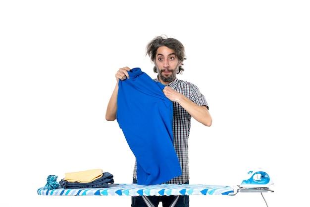 전면보기 젊은 남성 흰색 배경에 파란색 셔츠를 들고 가사 작업 철 남자 옷 깨끗한 기계 집