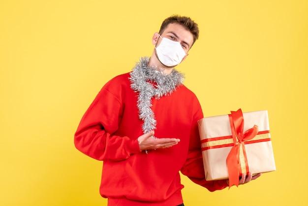 Вид спереди молодой мужчина держит рождественский подарок в стерильной маске