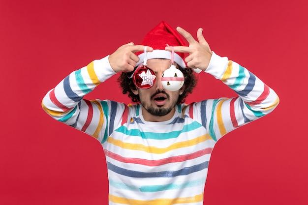 赤い壁の新年の赤い休日にクリスマスツリーのおもちゃを保持している正面図若い男性