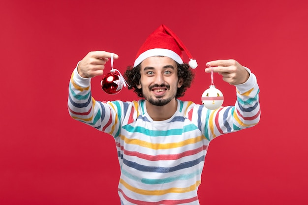 赤い机の新年の赤い休日にクリスマスツリーのおもちゃを保持している正面図若い男性