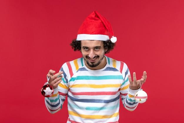 赤い壁の赤いモデルの新年の休日にクリスマスツリーのおもちゃを保持している正面図若い男性
